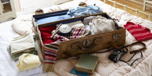 Items in suitcase on bed.