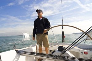 The skipper of a yacht takes the wheel