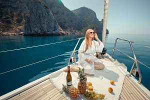 beautiful-young-girl-eating-and-talking-on-a-mobile-phone-on-a-boat-sailing-along-the-rocky-shore-of-the-sea